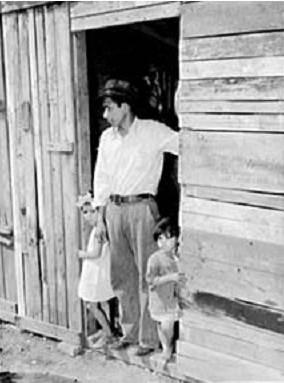 شکل1.پدرمکزیکی و کودکان در راهرو ورودی منزل خود که از الوار ساخته شده است.